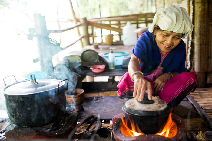 An environmental portrait of a cook working in her traditional Karen kitchen.