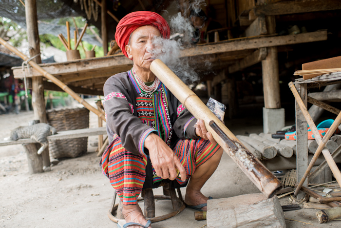 An environmental portrait of a Lahu man outside his house smoking