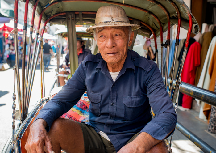 Environmental portrait of a contemplative tricycle taxi rider in Thailand