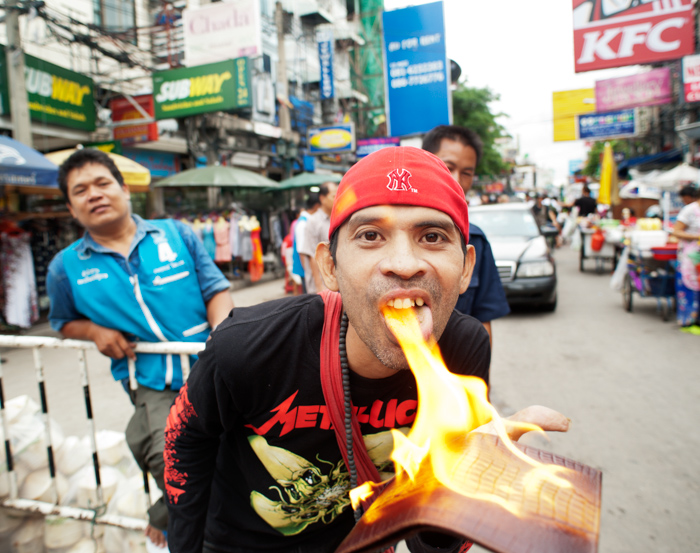 An environmental portrait photo of a street vendor in Khao San Road, Bangkok, demonstrating the product he is selling is genuine crocodile skin by pouring lighter fluid on the wallet and setting it on fire