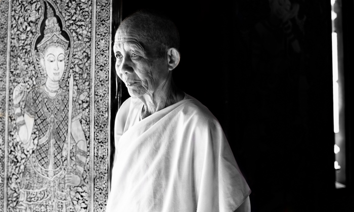 Atmospheric black and white environmental portrait photography of a Buddhist nun