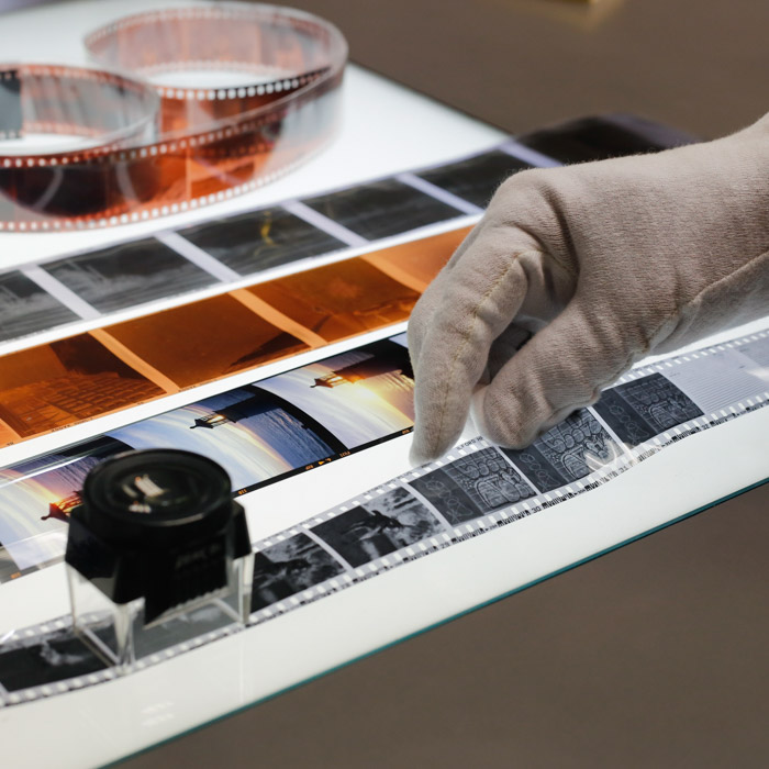 A shot of a gloved hand handling analog film negatives