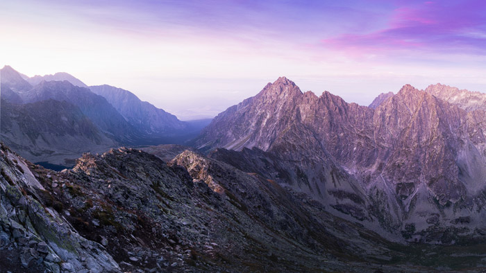 A breathtaking mountainous landscape with purple tinged sky