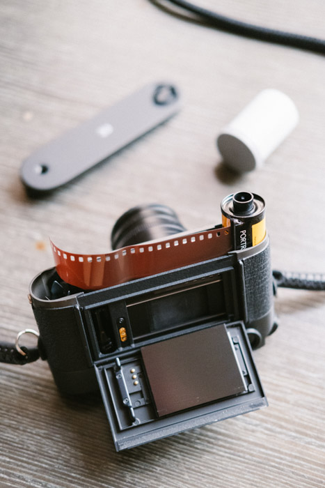 Overhead shot of an analog photography camera with rolls of film on a wooden tabletop