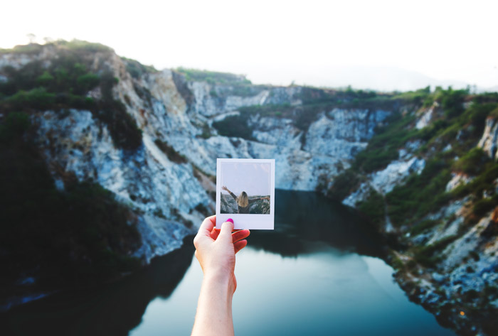 The photographer holds a polaroid of a girl over a mountainous landscape and lake