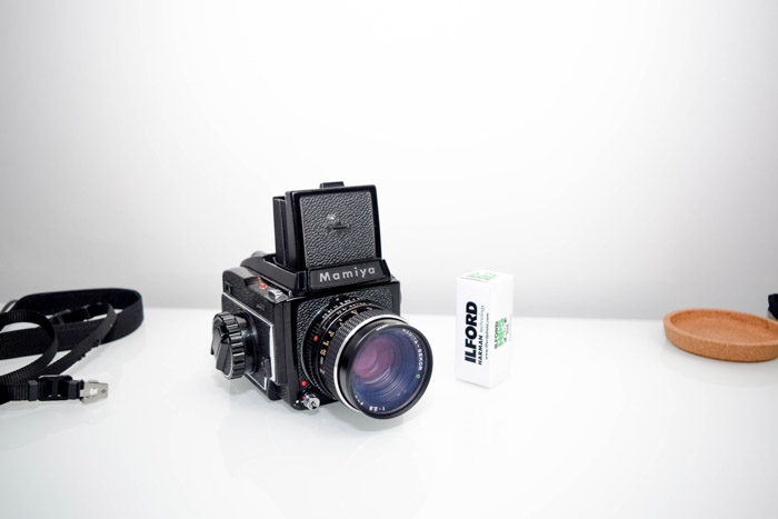 A mamiya film camera with a roll of film beside it on white background