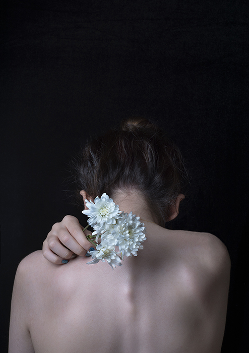 Artistic portrait of the back of a female model holding white flowers towards the camera