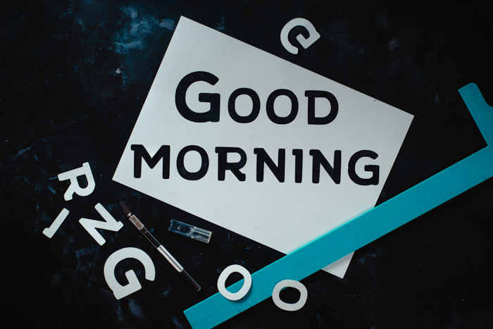"Stencil made of white paper with the text ""Good morning"" written on it, with additional white cutout letter and a paintbrush around the paper"