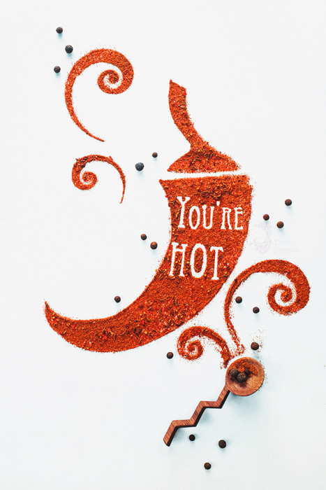 A food art shot with the words 'you're hot' created with spices in the shape of a paprika on white background