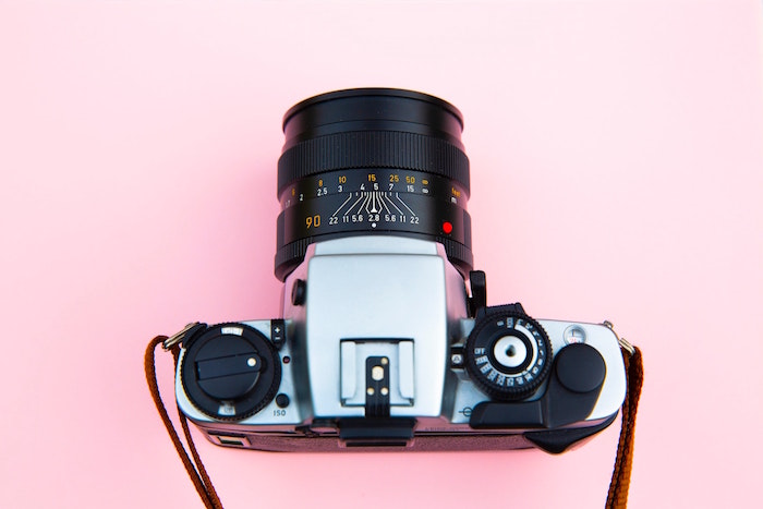 An overhead shot of a camera on pink background, food photography tips