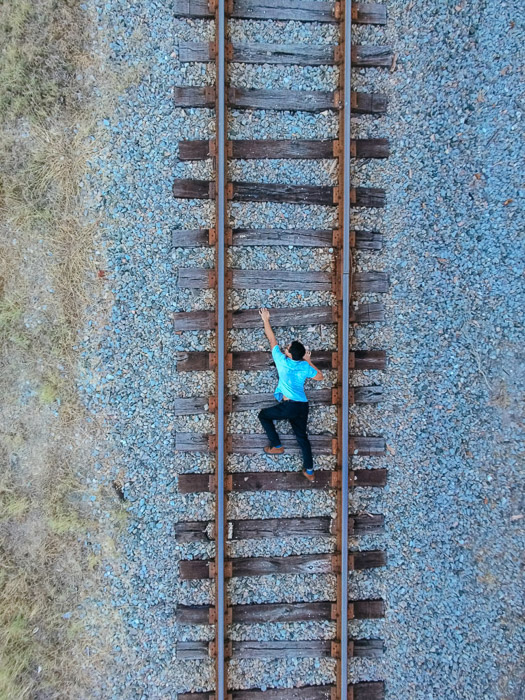 A photo of a man on train tracks, taken from overhead to give the illusion that he is climbing upwards