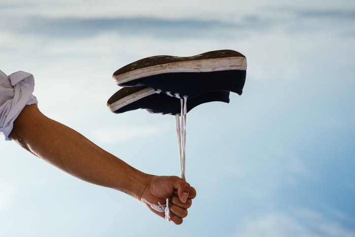 A person holding a pair of shoes by the laces which look like they are floating like a balloon