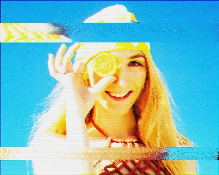 Analogue glitch art image of a girl holding a lemon to her head
