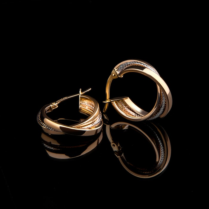 gold earrings on a black background