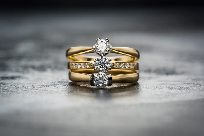 three gold rings with diamonds stacked on top of each other