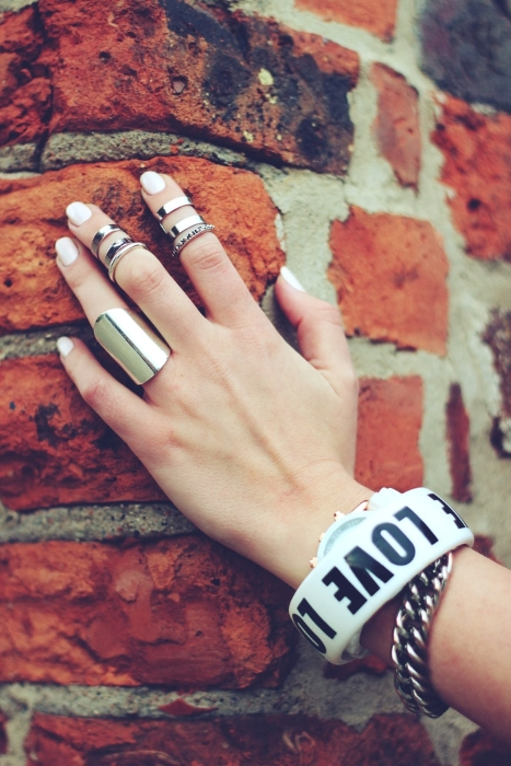 hand on a brick wall with rings and bracelets