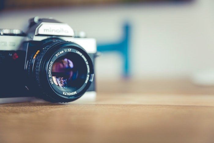 A camera on a wooden table with soft blurry background