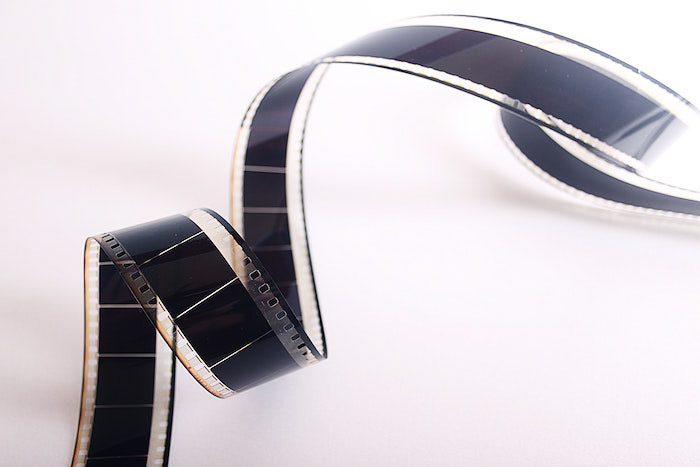 A film photography nagtive strip on white background - how to become a successful photographer