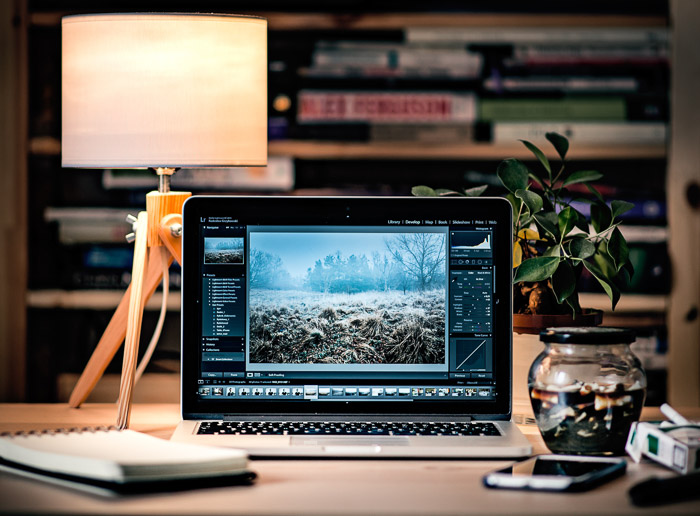 A laptop, notebook, phone and other items on the table of a professional photographers office