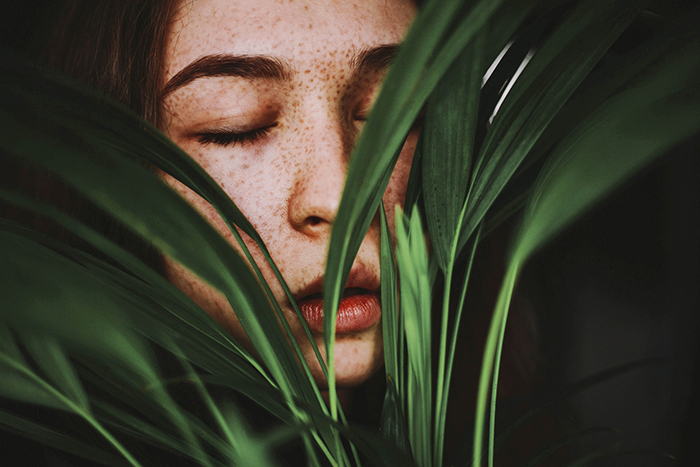 Atmospheric indoor photography portrait of a girl pushing her face between the leaves of a houseplant