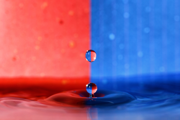 A red and blue background with a water drop photography splash in the foreground