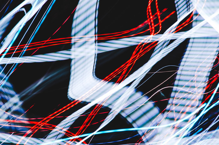 Strips of blurry white and red light trails on black background