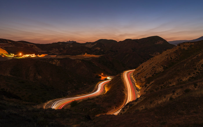 A winding road illuminated by light trails running through a magnificent mountainous landscape in low light