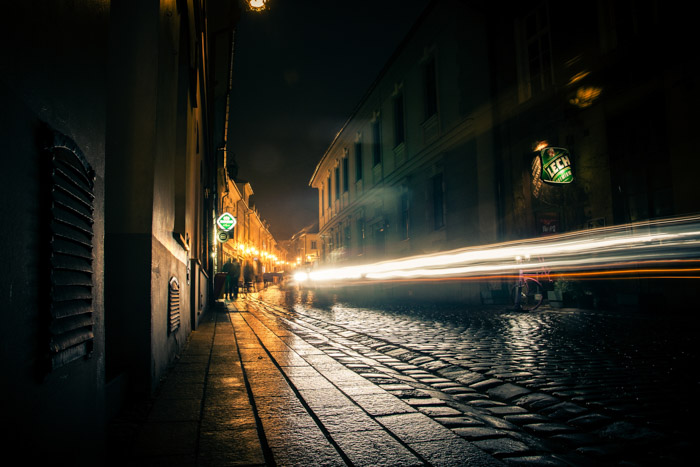 Atmospheric cobblestone street view at night with a stream of light trails shooting down the road.
