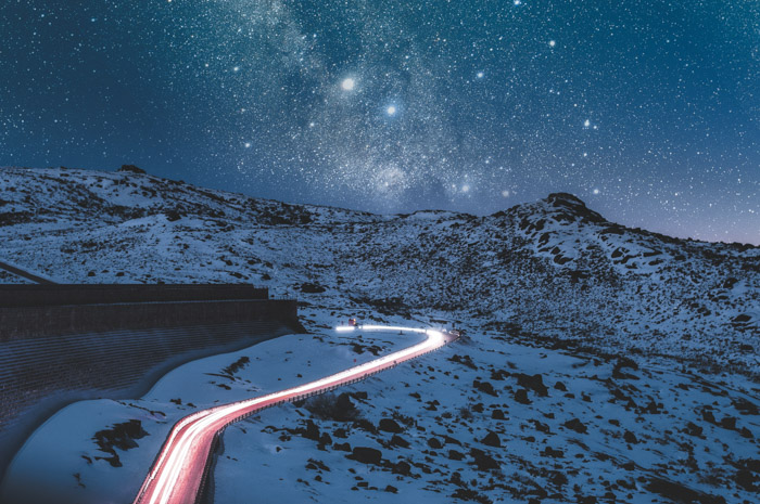 A road illuminated by light trails running through a snowy landscape under a fantastic night sky filled with stars.