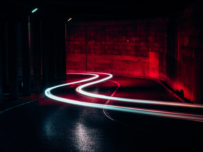 The white light trails of a solitary car running through a tunnel
