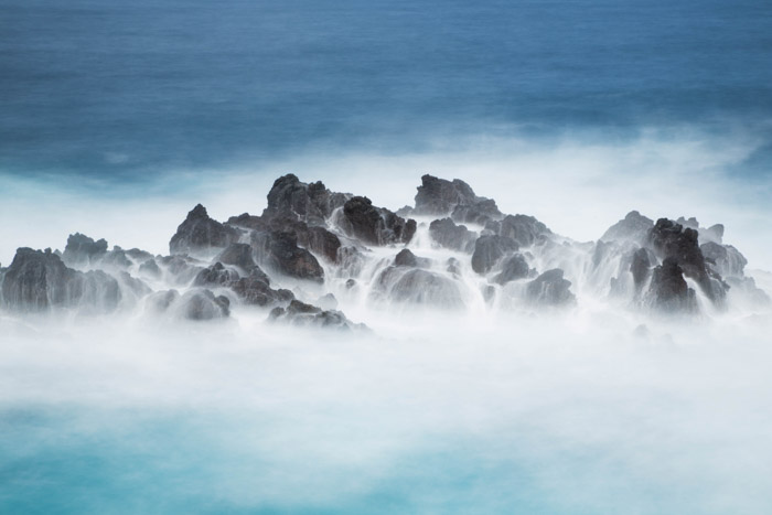 Misty over rocks in the ocean captured through long-exposure