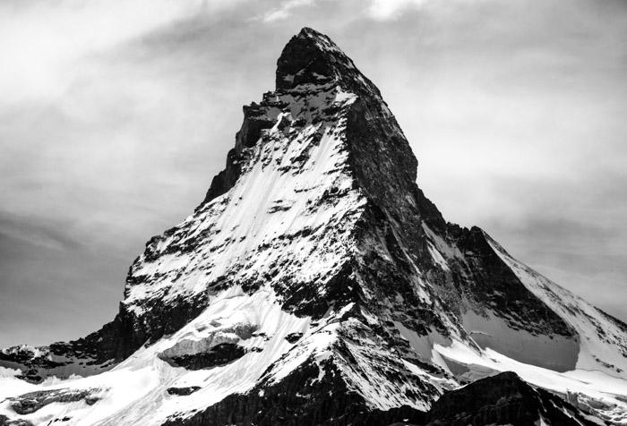 A monochrome image of a snowy mountain peak