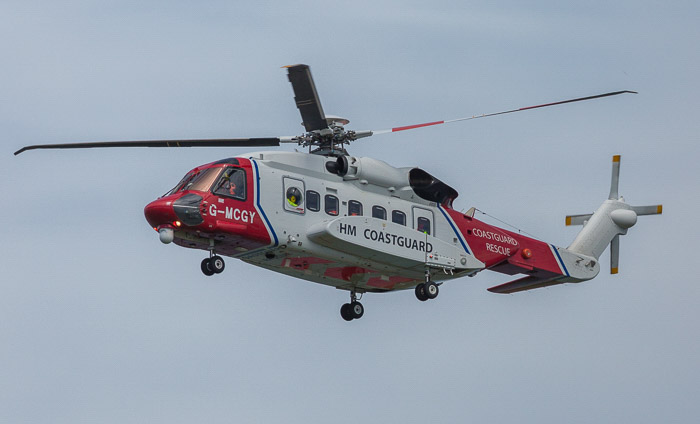 A helicopter in mid flight, its rotors look strangely static due to motion blur photography