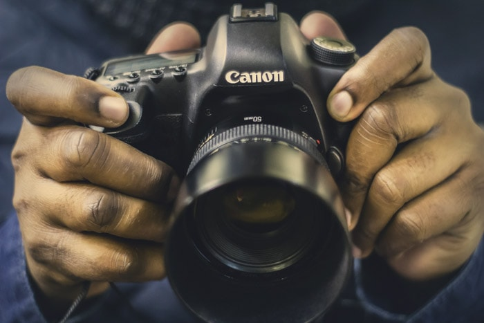 Close up of someone holding a Canon DSLR fitted with a 50mm Nifty Fifty Prime lens