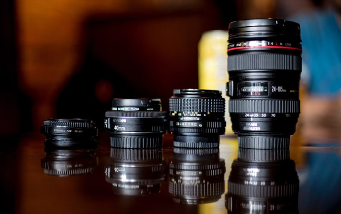 Four different camera lenses on a brown surface - why you need a nifty fifty