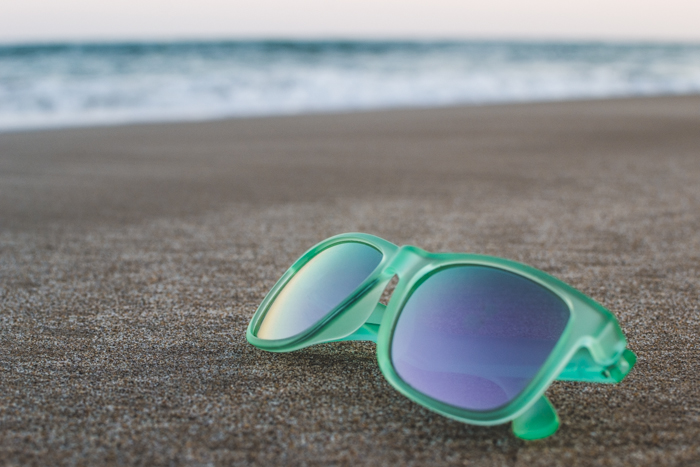 A pair of green framed sunglasses resting on the sand, the seas waves blurred in the background
