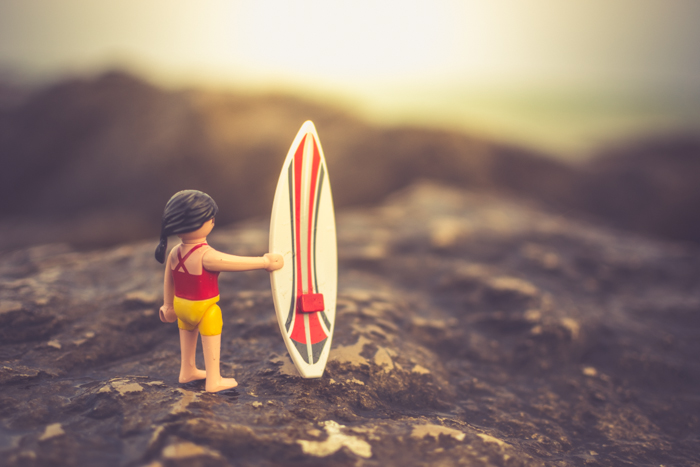 A playmobil character with a surfboard posed on a rocky beach, creative beach photography ideas.
