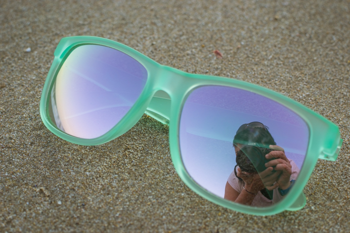 A pair of green framed sunglasses resting on the sand with the photographers reflection in one glass, cool beach photography ideas.