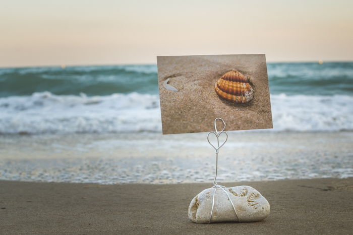 A DIY photo holder made from beach stones on the sand, a fabulous seascape in the background