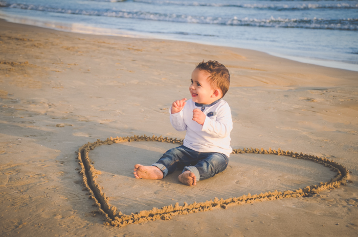 A young boy sits in the middle of a love heart drawn in the sand, creative beach photography ideas.
