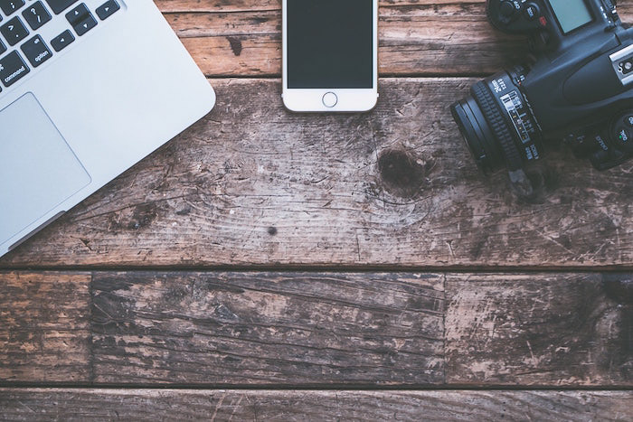 Overhead shot of photography equipment on a wooden table - photography insurance tips