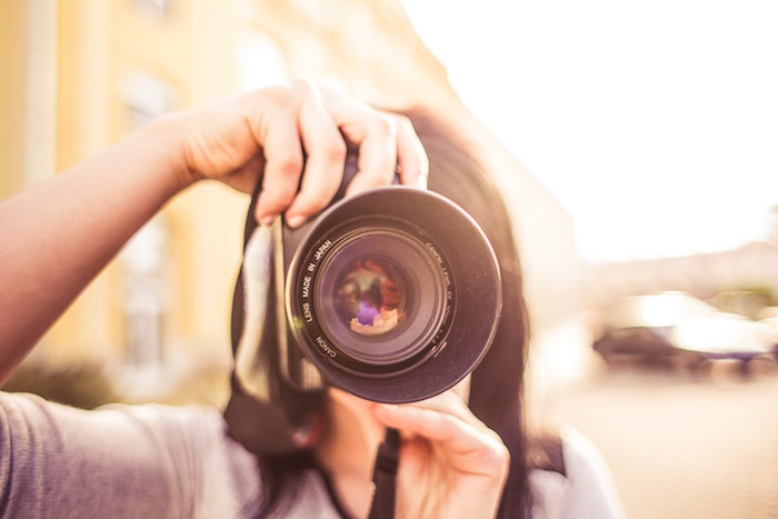 A girl pointing a camera towards the photographer on soft blurry background - photography and camera insurance tips