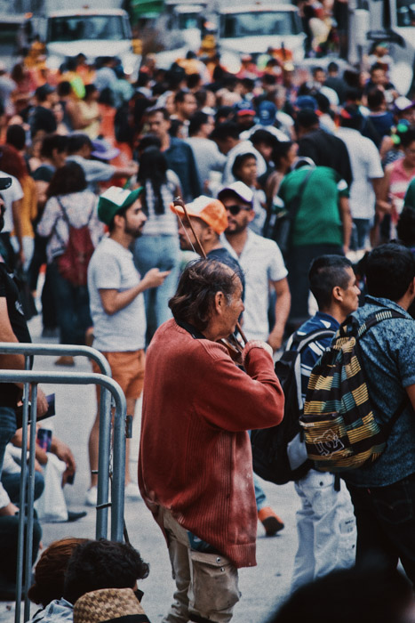 A crowded street scene focused on a man playing the fiddle - photography laws by state