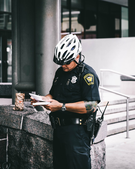 A street photo of a policeman writing in a notebook