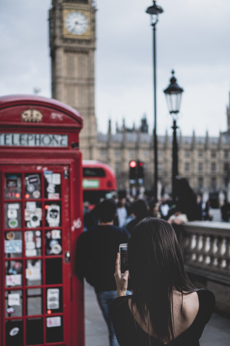 A blurry photo of a girl taking a smartphone photo of Big Ben in London - street photography laws