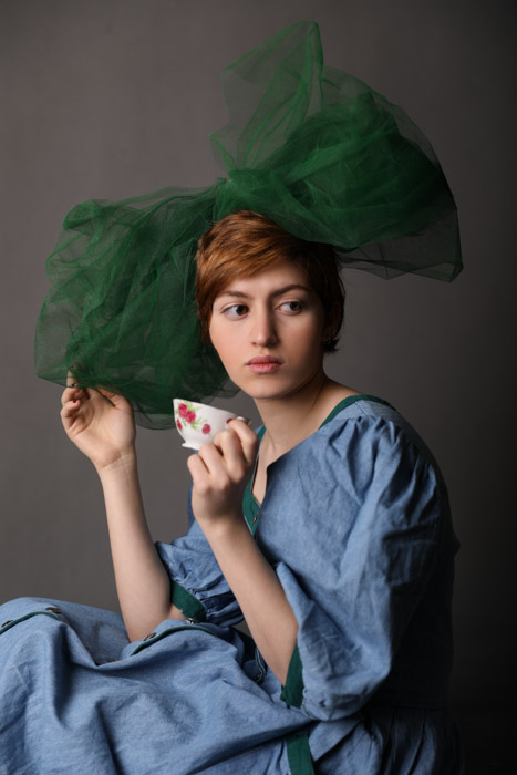 A studio portrait of a young woman posing with large green hair bow and a teacup against a grey background - photography lighting