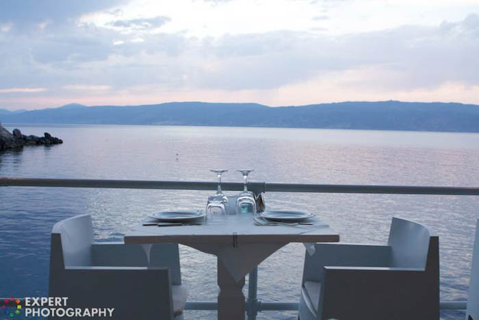 A dining table set up by the sea at evening time