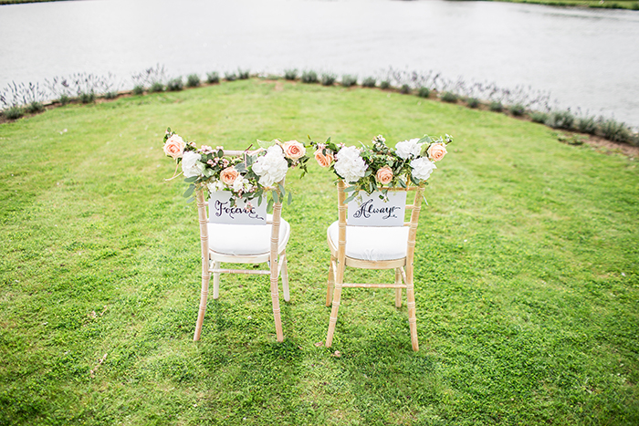 A bright and airy photo of two decorated wedding chairs to be used as wedding portrait backgrounds