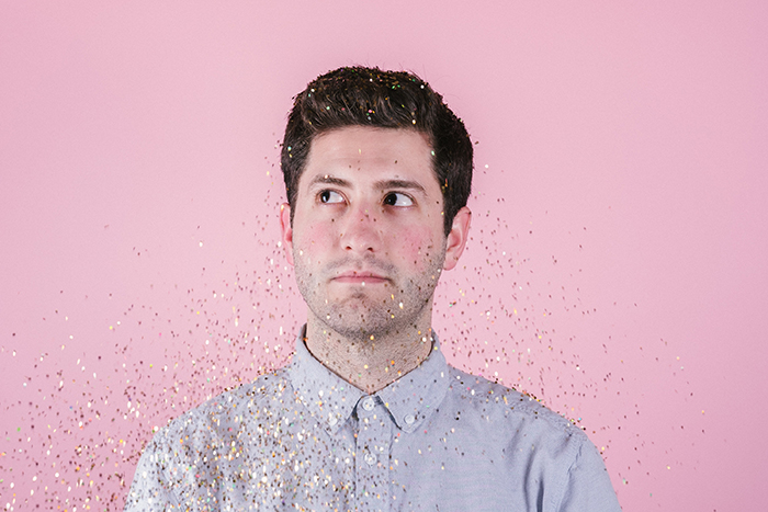 Portrait of a man covered in falling glitter posing in front of a pink photography background