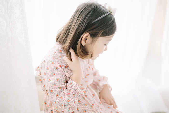 Portrait of a little girl sitting in front of a soft white backdrop